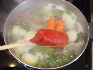 Once the soup is boiling at a rapid pace add in a half can of tomato paste.