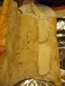 Shown: the bread with crumb removed and with a sprinkle of grated cheese and two slices of the mozzarella