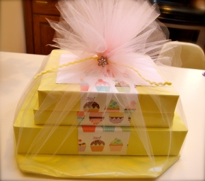 Took a yellow paper then wrapped a piece of printed paper around - stacked gifts and tied into less than a yard of tulle.  Tied the top with an elastic then fastened a jewel on it. Super cute right?