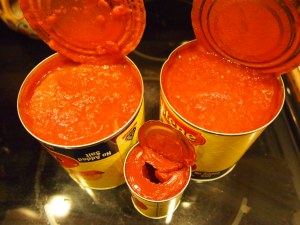 Shown two cans of kitchen ready tomatoes and tomato paste