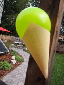 Ice Cream cone decorations I made. The photo is blurry sorry. But this is a vibrant colored balloon inflated and glued into a piece of paper printed and rolled to look like a waffle cone.  I hung them all around the yard and inside the house.