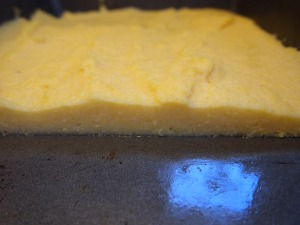 Cooled polenta in a pan, cut to show thickness.