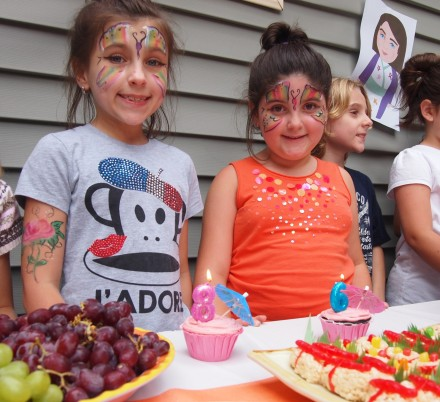 The girls all out of their outfits and ready to blow out their candles.