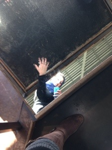 A photo of me in the mirror looking down touching a giant pin art table. (you kno the ones we would put on our faces as kids?)