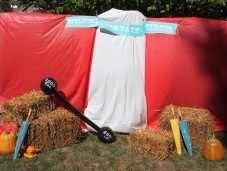 I used plastic table cloths, hay bales, umbrellas from another party, a strong man barbell balloon, a handmade sign and pumpkins. Then on the side I had photo booth props for everyone.