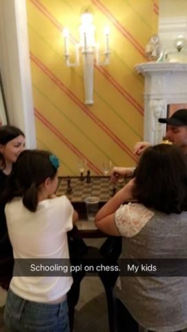 At happy hour, the girls (who are whips at chess) are helping this cute girl beat her bf at chess.. they loved the kids so much. :)