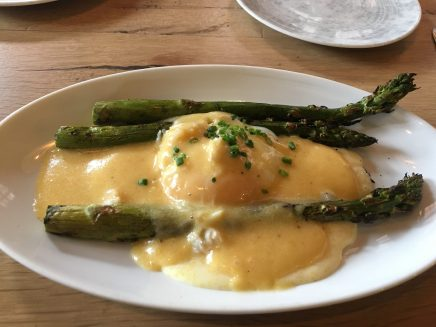 Asparagus w soft egg over grits with hollandaise.