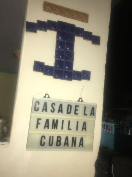 The blue T-like shaped symbol is the symbol for casa particular, a rental room or home.