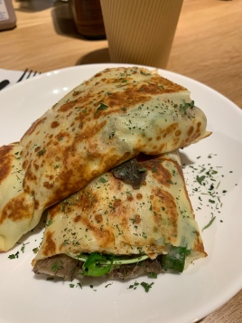 Savory crepe with cheese, mushrooms, asparagus, and arugula.